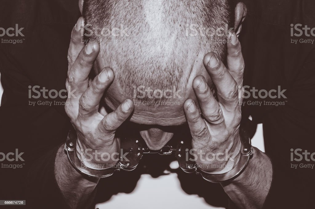 Arrested criminal. Arrested criminal with handcuffs on his hands sitting at the white table in  police station. Crime concept. stock photo