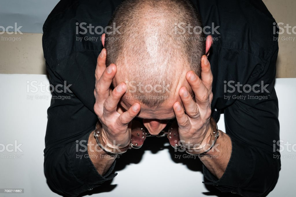 Arrested criminal. Arrested criminal with handcuffs on his hands sitting at the white table in the police station. Crime concept. stock photo