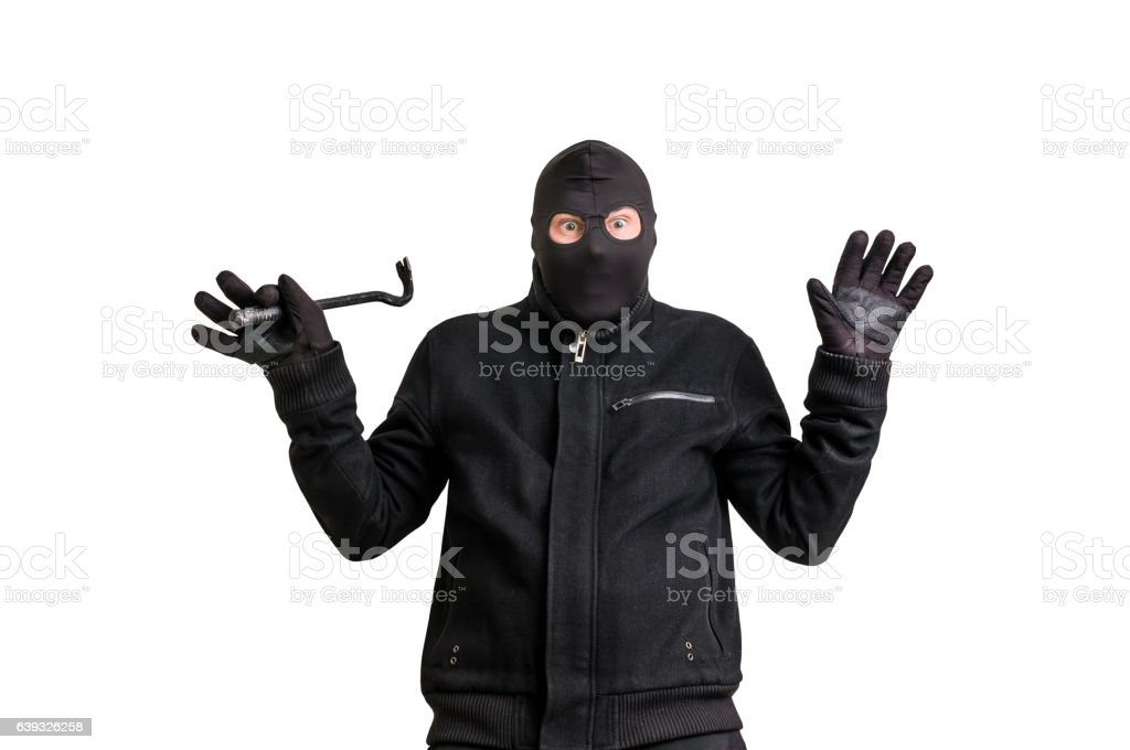 Arrested thief in balaclava with crowbar and raised arms stock photo
