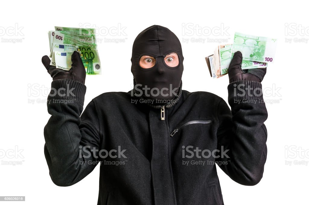 Arrested thief in balaclava with stolen money and raised arms stock photo