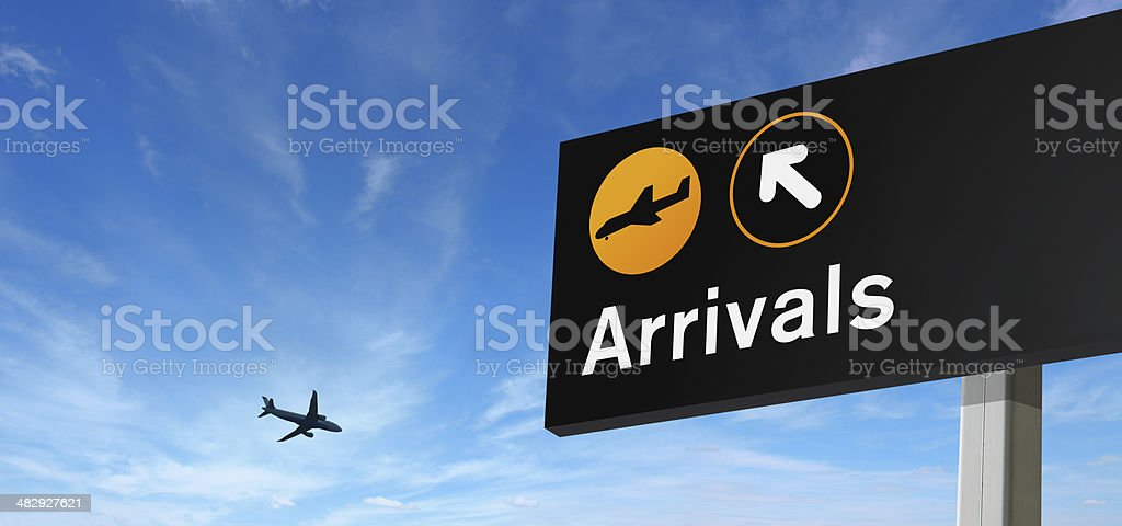Arrival Sign and Airplane on the Sky stock photo