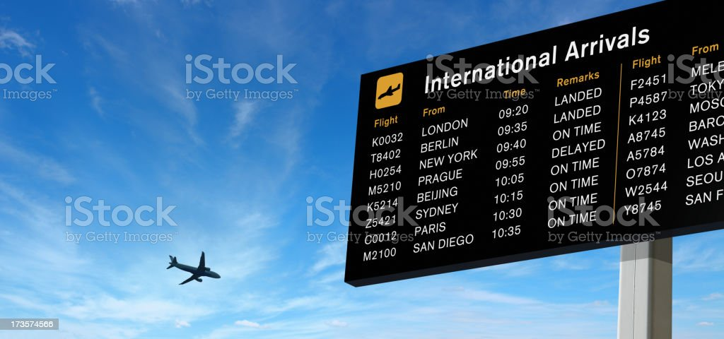 Arrivals Board and Airplane on the Sky stock photo