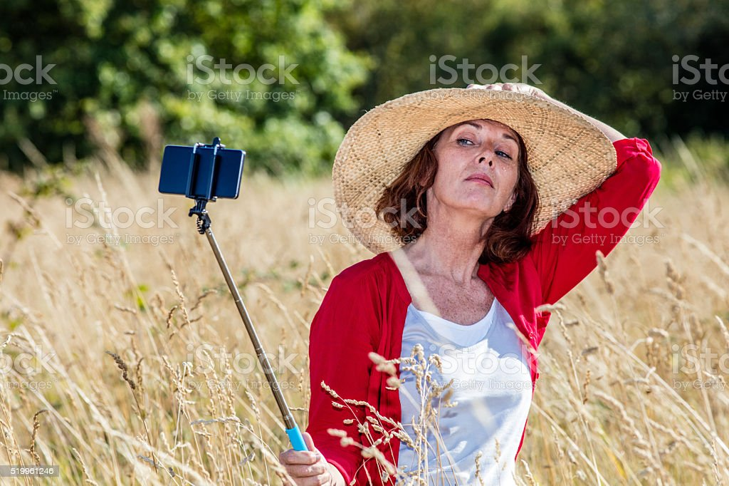 arrogant 50s woman making a self-portrait on mobile phone stock photo