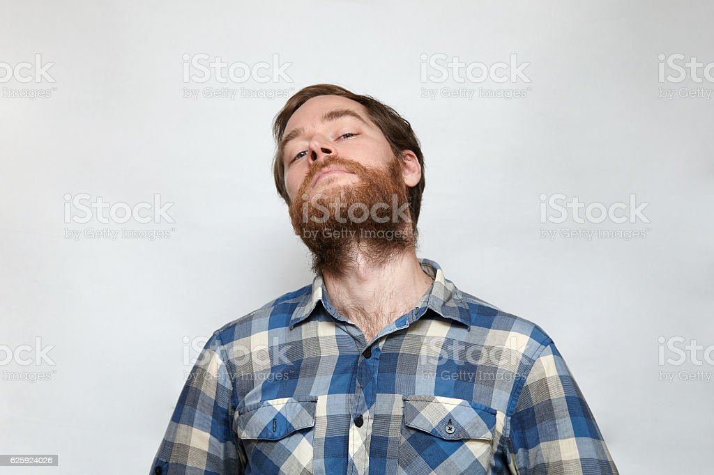Arrogant man with thick beard lifts up his chin stock photo