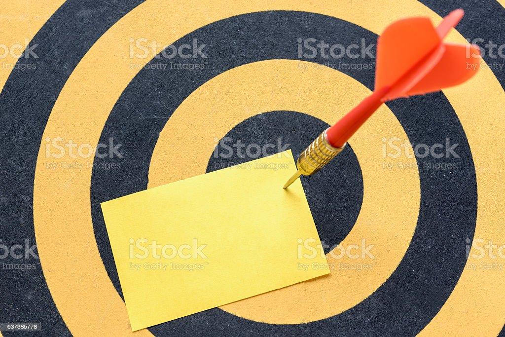 Arrow hitting yellow blank note over in bullseye on dartboard stock photo