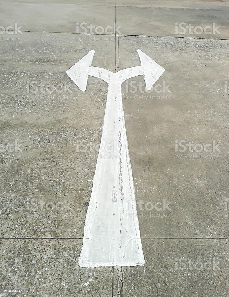 arrow in two directions on asphalt stock photo