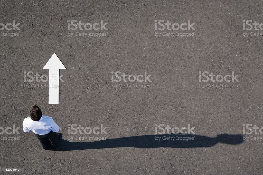 Arrow on pavement pointing away from businessman stock photo