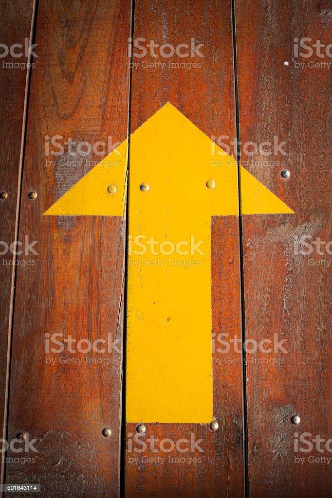 Arrow on wood floor background stock photo