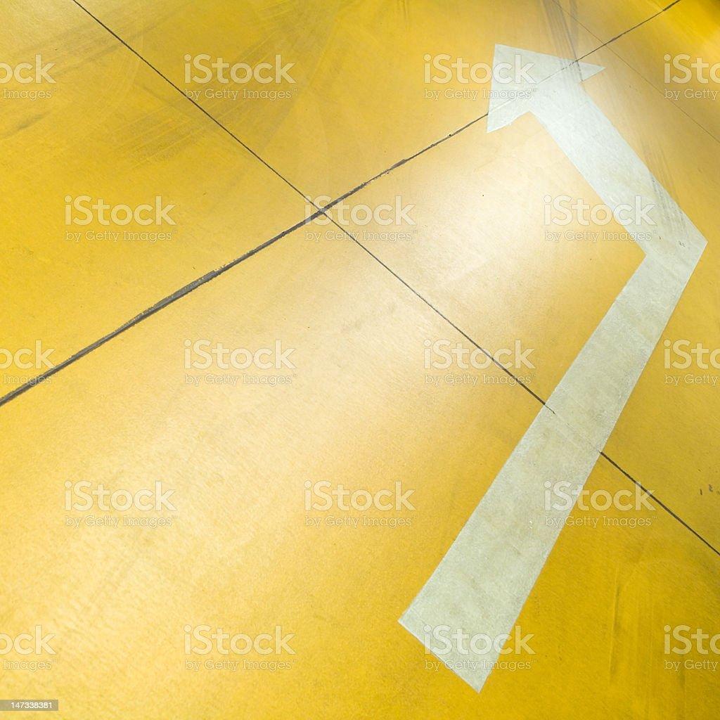 Arrow on yellow parking garage floor royalty-free stock photo