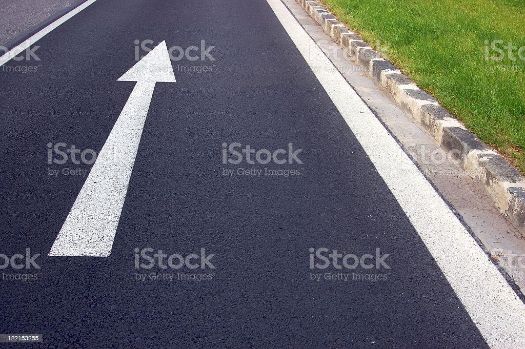 Arrow pointing forward on road asphalt stock photo
