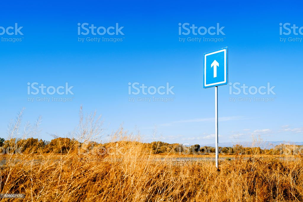 Arrow road sign against blue sky in the fall stock photo
