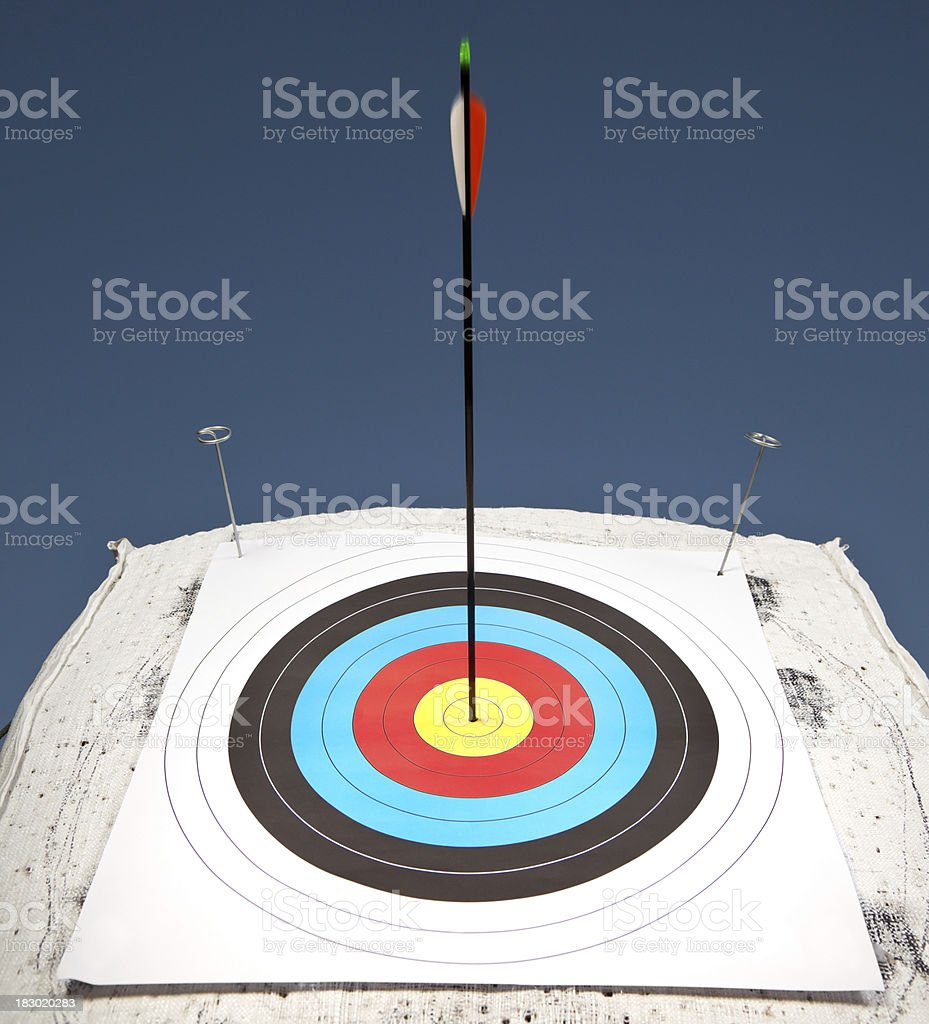 Arrow strikes the bull's-eye of an archery target royalty-free stock photo