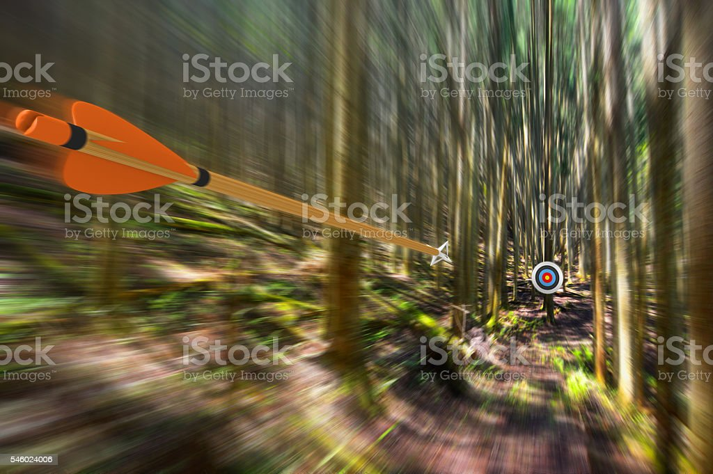 Arrow traveling through air at high speed to archery target stock photo