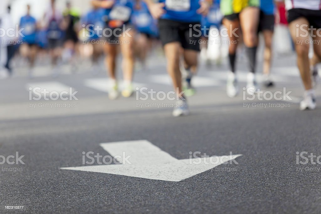 Arrow with line of runners at city marathon royalty-free stock photo
