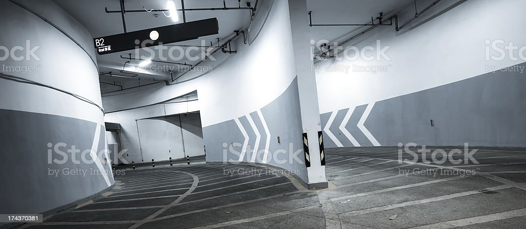 Arrows point the way inside of a city parking structure. stock photo