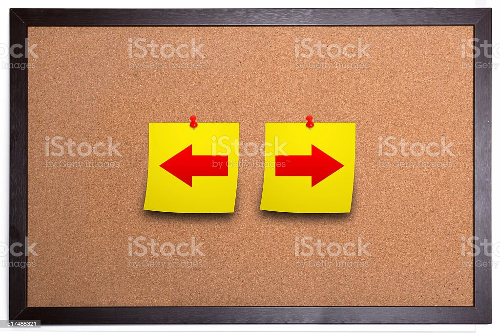Arrows sign on corkboard with adhesive note stock photo