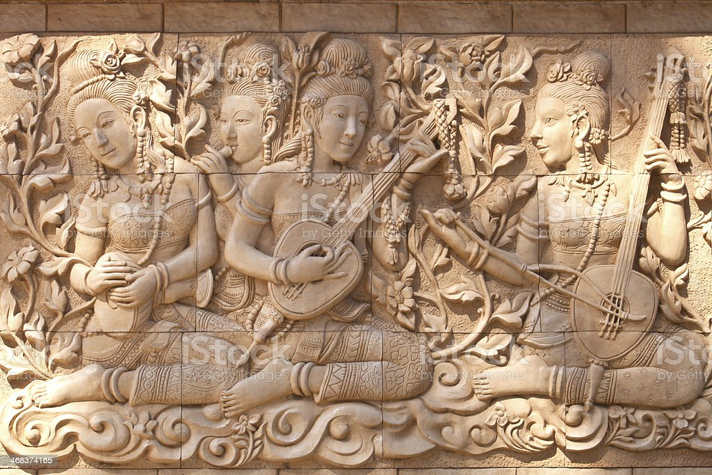 Art clay wall decoration, lady play music, Thai scullpture stock photo