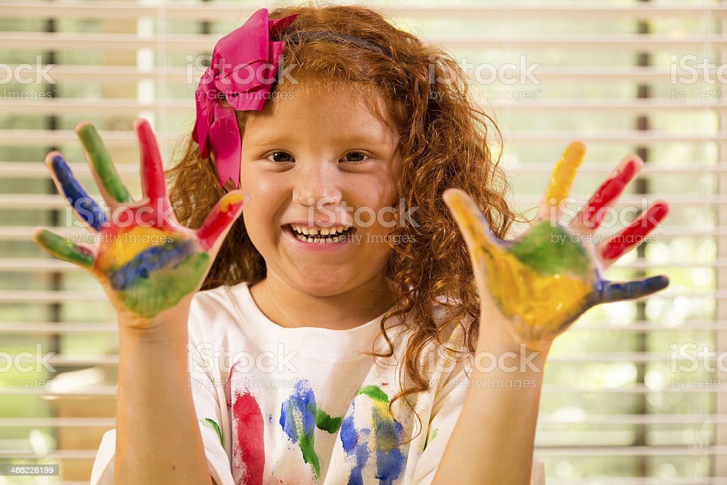 Art:  Elementary girl shows her painted hands in art class. royalty-free stock photo
