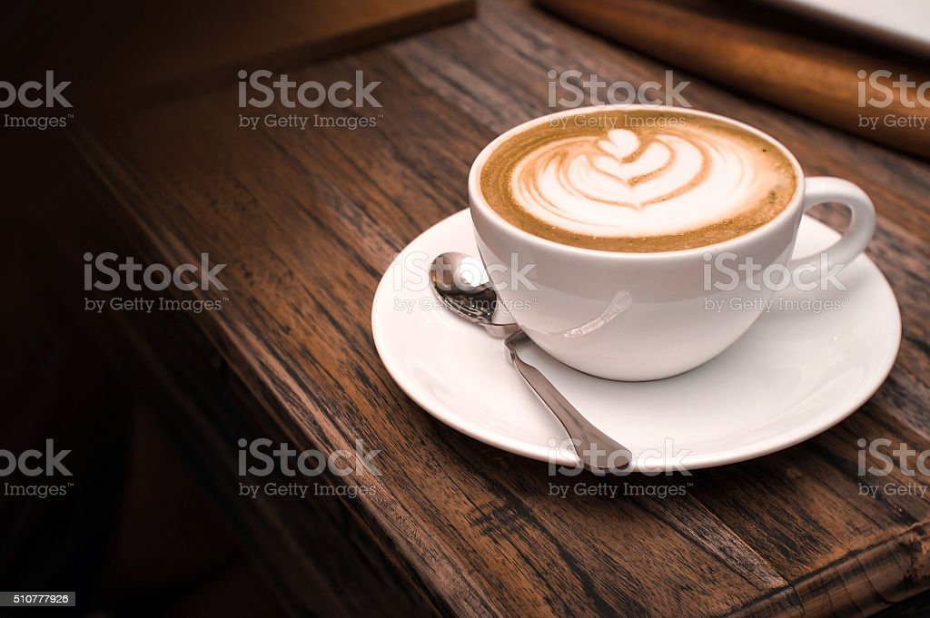 Art latte a cup of hot coffee on wooden table stock photo