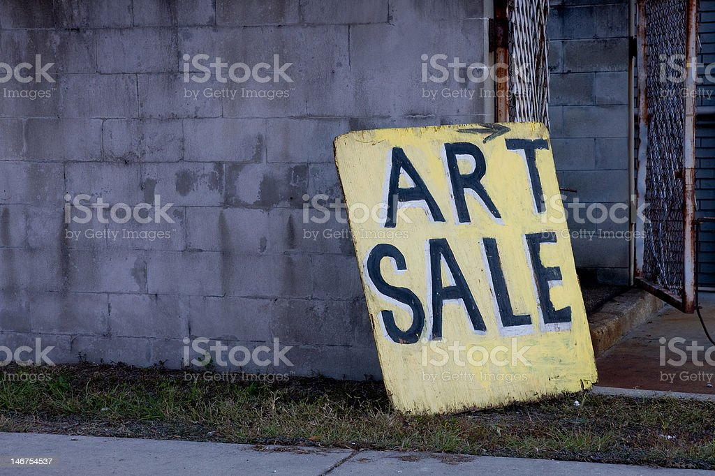 Art Sale Sign Board on Right Leaning Against Block Wall stock photo