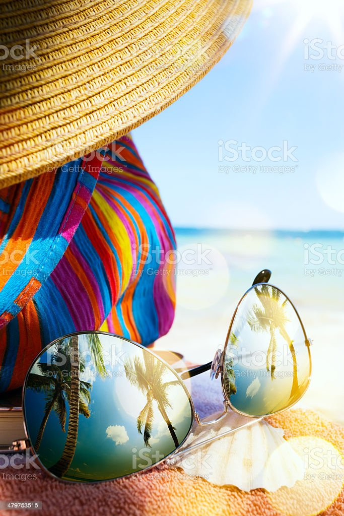 art Straw hat and sun glasses  on a tropical beach stock photo