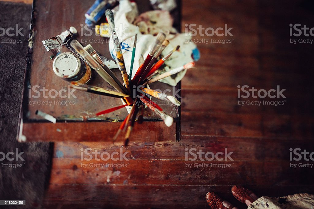 Art studio wooden table with paintbrushes paint tubes and rag stock photo