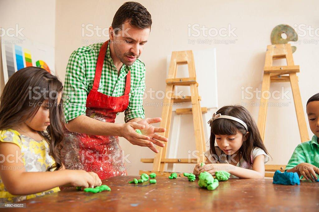 Art teacher during sculpting class stock photo