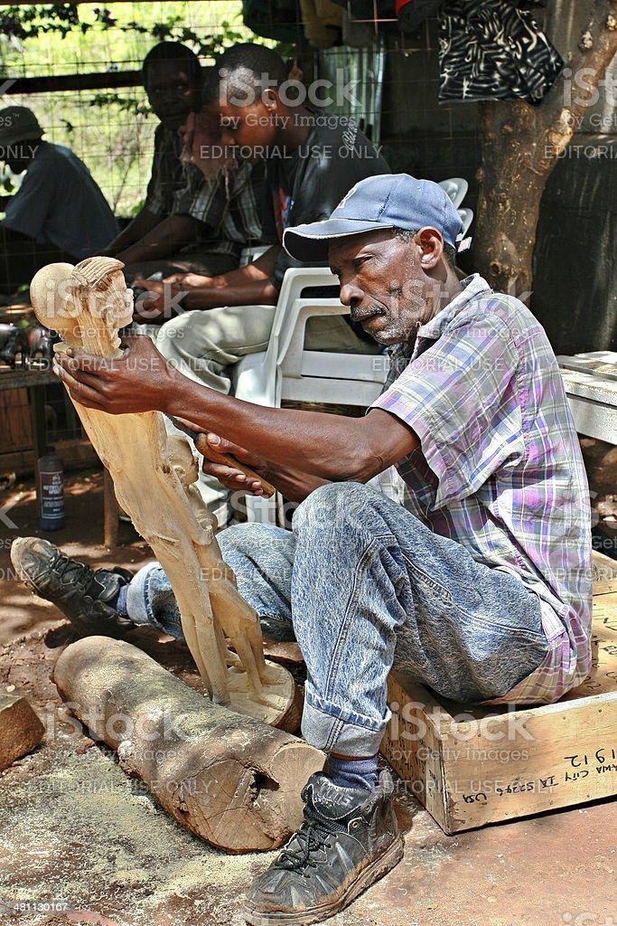 Art workshop outdoors woodcarver carves Maasai figurines. stock photo