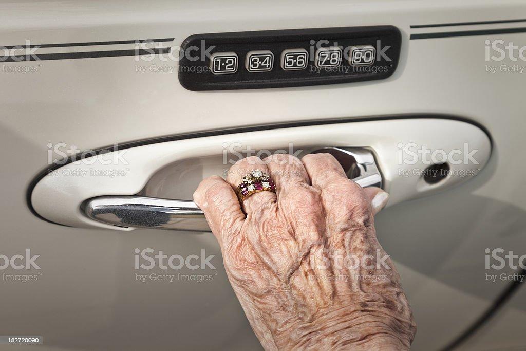 arthritic hand of senior woman opening car door royalty-free stock photo