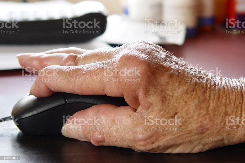 Arthritic hand using a computer mouse. royalty-free stock photo