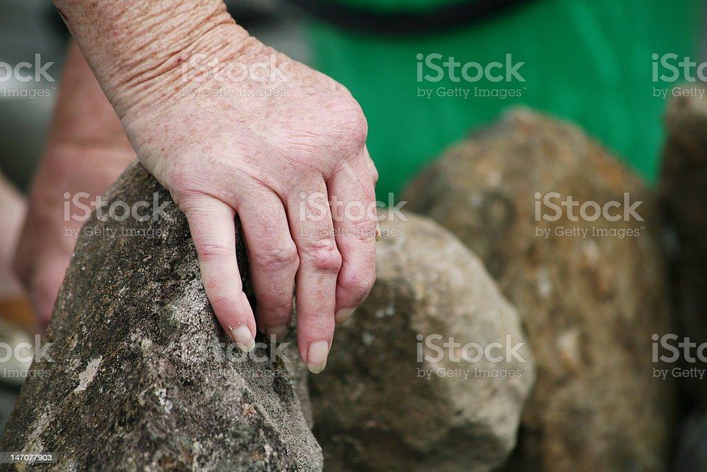 Arthritic hands moving rocks. royalty-free stock photo
