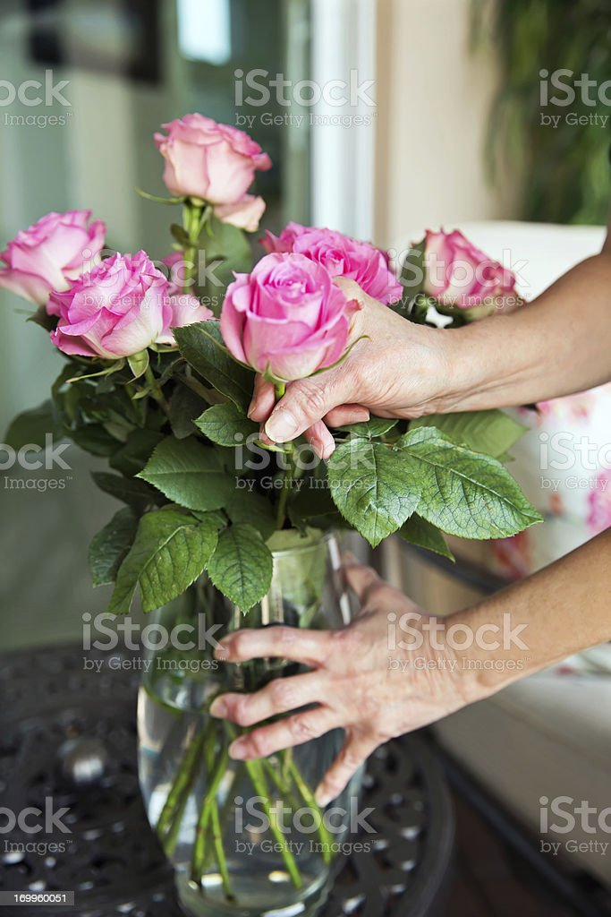 Arthritis: Arthritic senior hands holding a flower vase stock photo