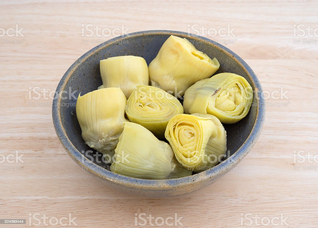 Artichoke hearts in a bowl on a wood table top stock photo