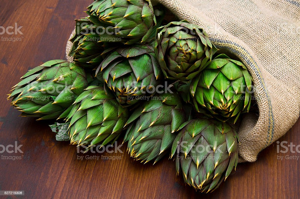 artichoke in burlap sack on wood stock photo