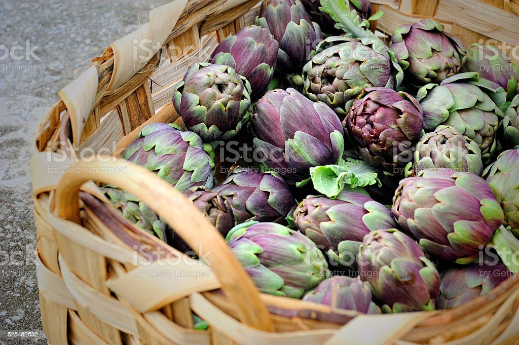 artichokes in wicker basket closeup stock photo