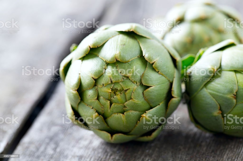 artichokes on wooden surface stock photo