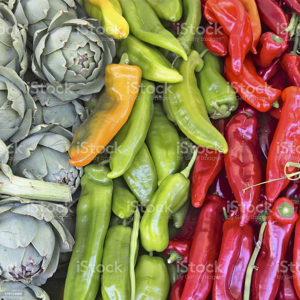 Artichokes & peppers on sale in a market royalty-free stock photo