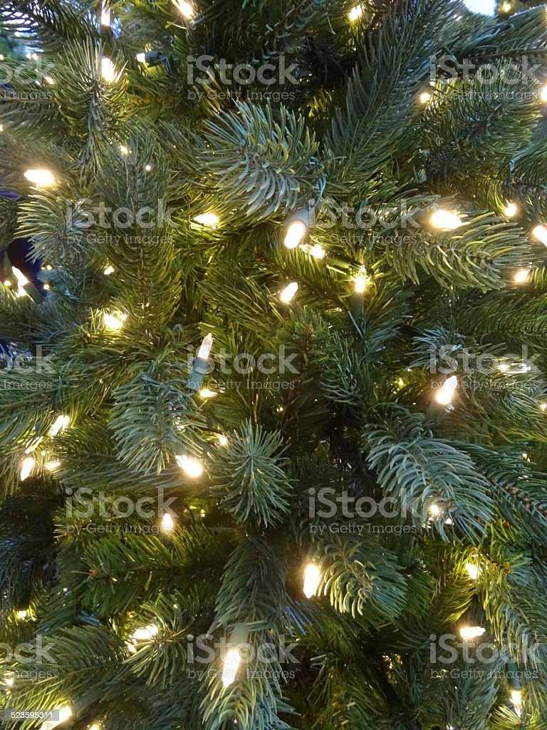Artificial Christmas tree decorations, green foliage-needles, white LED fairy lights stock photo