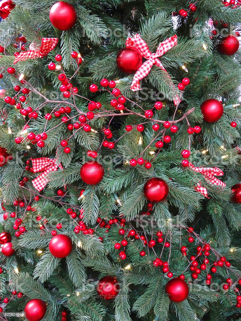 Red Decorated Christmas Tree - Artificial christmas tree with red decorations baubles berries ribbon bows royalty free