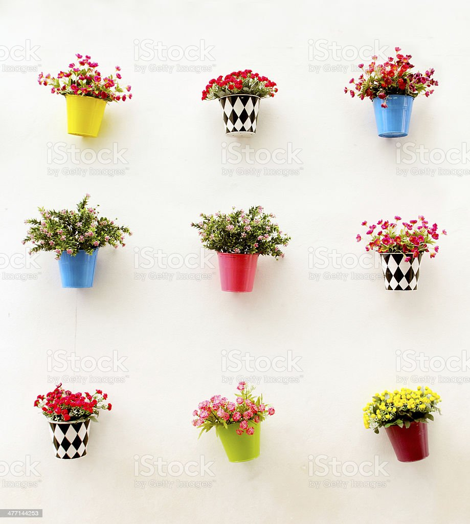 Artificial colorful flowers pots hang onto the wall royalty-free stock photo