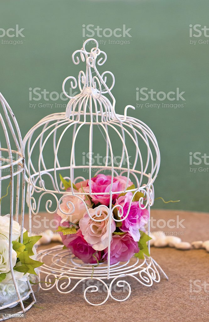 Artificial flowers bunch in white birdcage. royalty-free stock photo