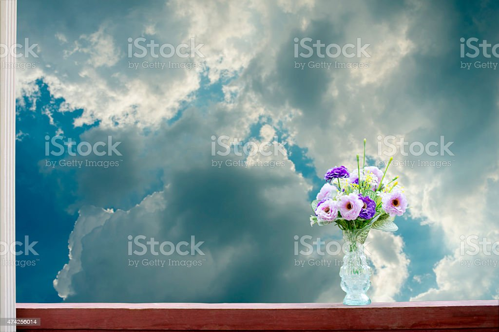 Artificial flowers in a vase on a sky background royalty-free stock photo