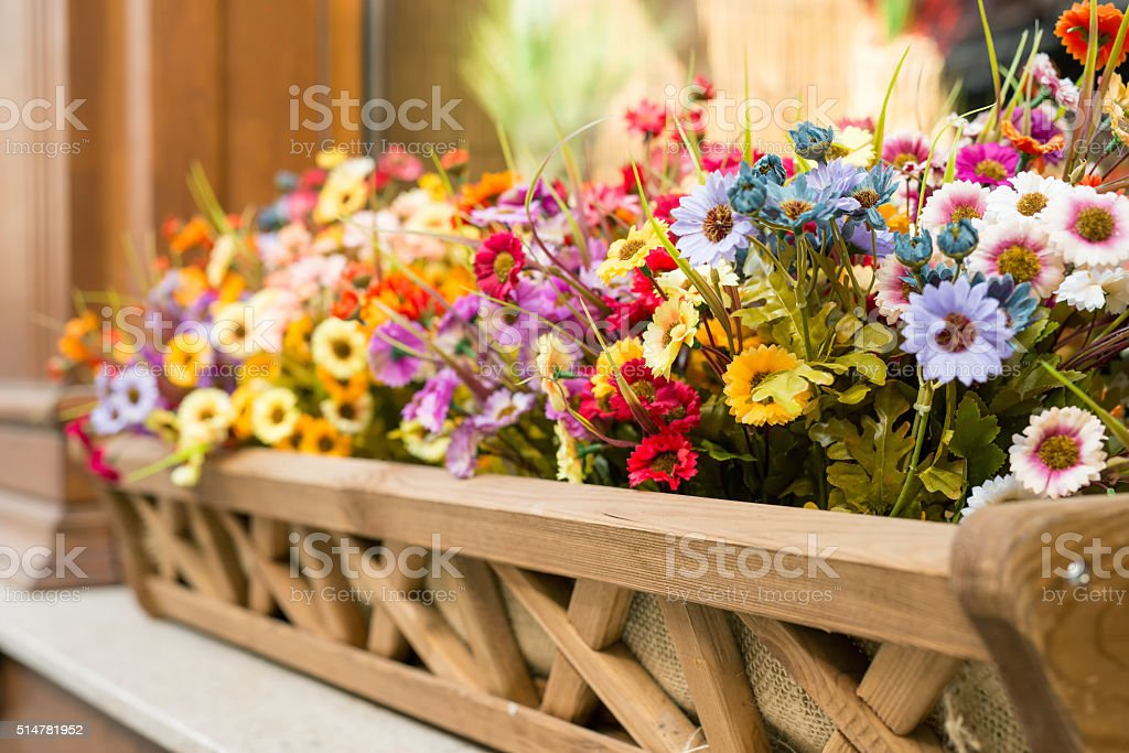 Artificial flowers in the box outside the window stock photo
