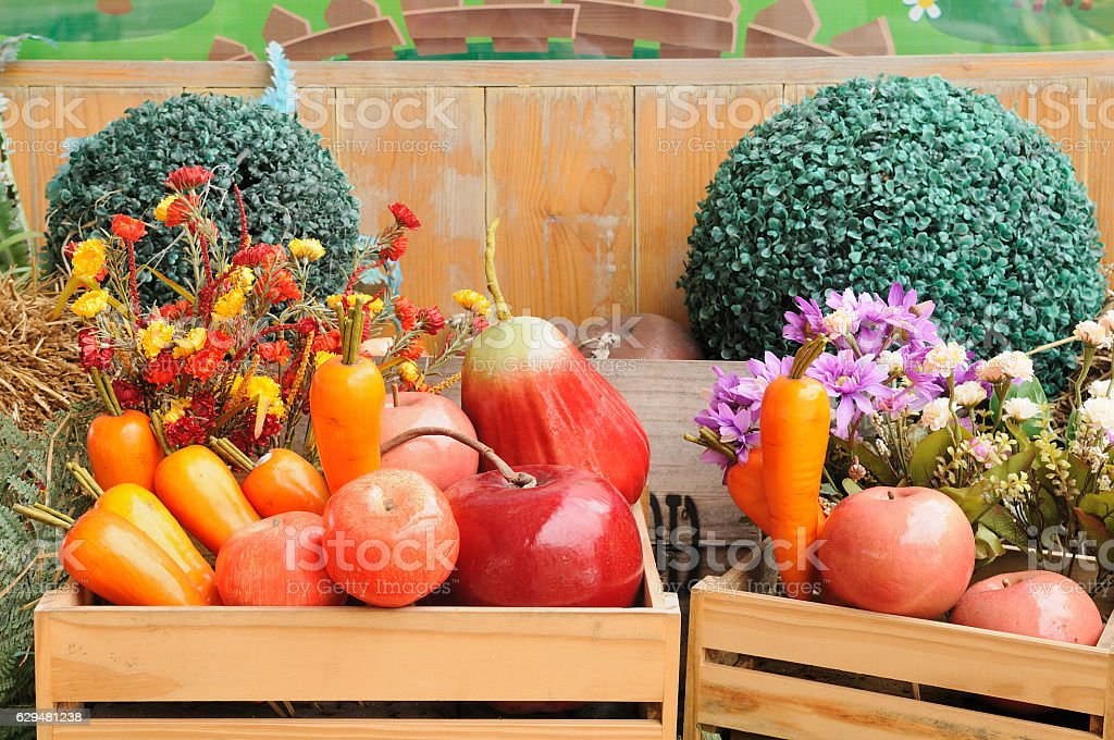 Artificial fruits in wooden boxes lay on pile of straw stock photo