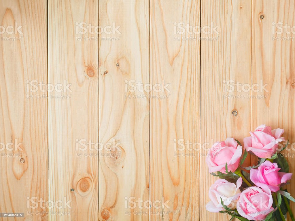 Artificial pink rose on wooden background stock photo