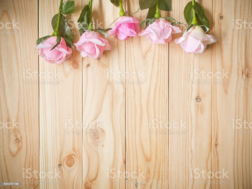 Artificial pink roses on wooden background with copy space stock photo
