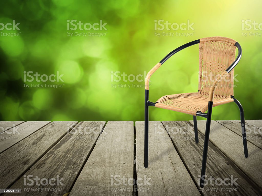 artificial rattan chair on wood,Bokeh green background stock photo
