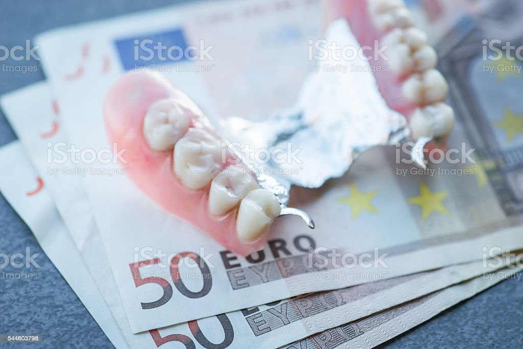 Artificial replacement teeth with money on a dark table stock photo