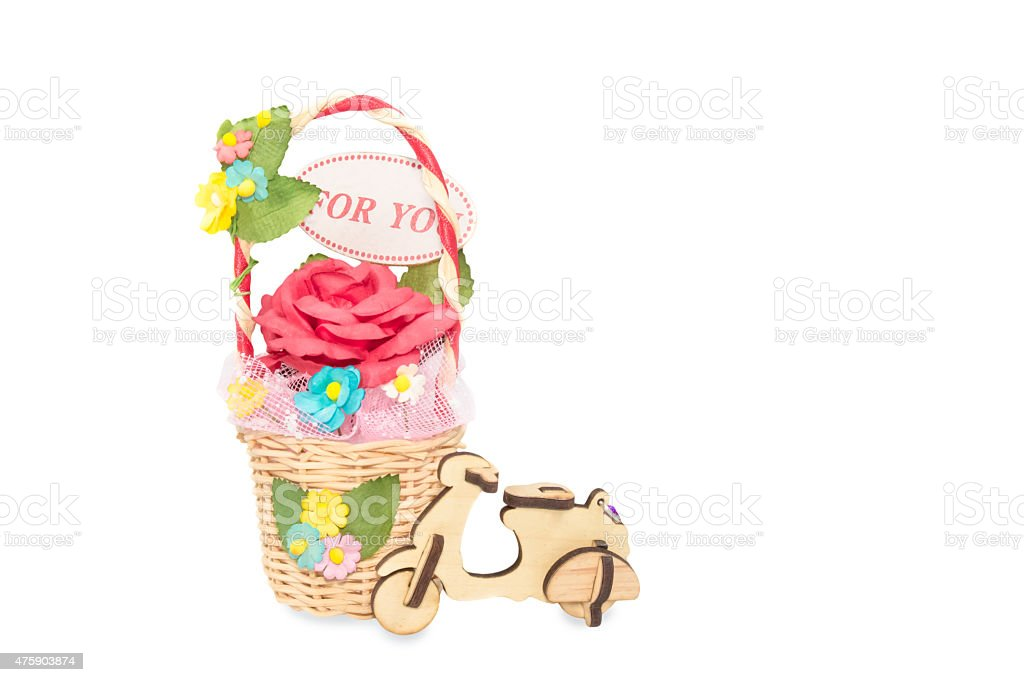 artificial roses in rattan basket with wooden toy motorcycle isolated stock photo