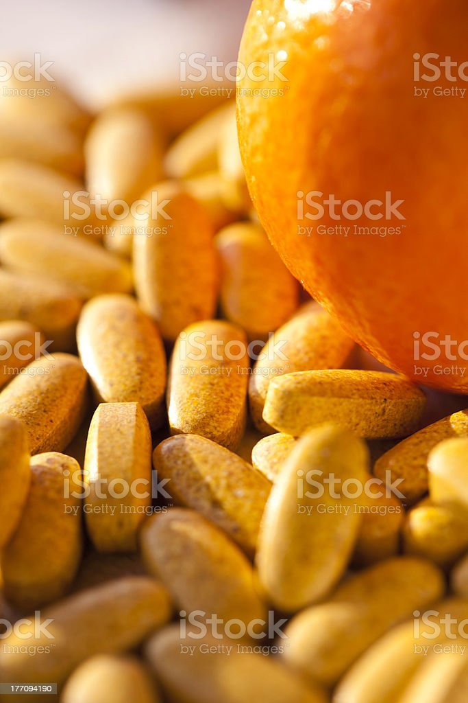 Artificial Vs Natural - Vitamin Pills And Orange royalty-free stock photo